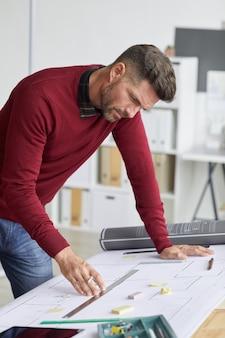 Vertikales seitenansichtporträt des bärtigen architekten, der blaupausen betrachtet, während er sich auf zeichentisch am arbeitsplatz stützt,