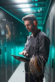 Vertikales seitenansichtporträt eines reifen netzwerkingenieurs, der während der wartungsarbeiten im rechenzentrum ein digitales tablet im serverraum verwendet