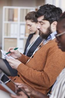 Vertikales seitenansichtporträt von leuten, die auf einer geschäftskonferenz in reihe sitzen, konzentrieren sie sich auf den bärtigen mann, der notizen in der mitte macht