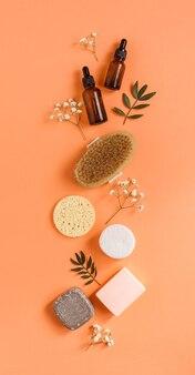 Vertikales set von reinigungskosmetik und zubehör. naturseife, schwämme, massagebürste, serum, öl.