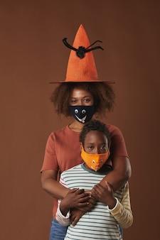 Vertikales studioporträt der modernen jungen frau, die den hexenhut trägt, der mit ihrem niedlichen sohn beide schutzmasken, braune oberfläche trägt