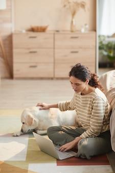 Vertikales, warm getöntes porträt einer modernen jungen frau, die laptop benutzt, während sie auf dem boden sitzt und hund in gemütlichem interieur streichelt