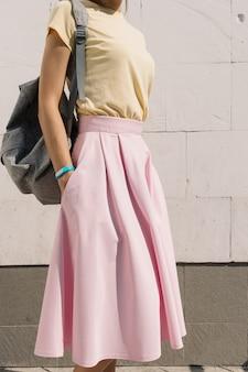 Vertikales zuschneiden des mädchens im gelben hemd, im rosa rock und im rucksack gegen die wand