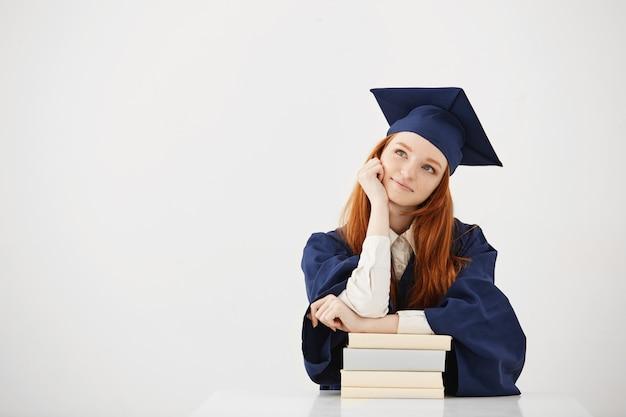 Verträumte absolventin, die lächelnd denkt, mit büchern sitzend.