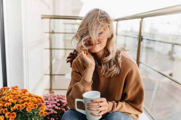 Verträumte blonde frau, die am balkon mit tasse tee sitzt. atemberaubende weibliche modell chillen auf der terrasse.