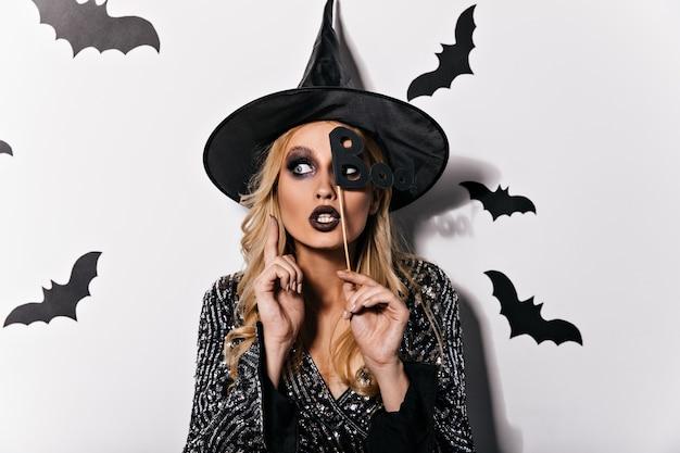 Verträumte blonde frau, die an halloween-partei aufwirft. innenfoto des eleganten vampirmädchens, das karneval genießt.
