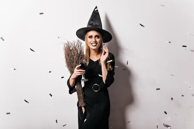 Verträumte böse hexe, die wein trinkt. ekstatische junge frau mit den blonden haaren, die an halloween-partei lächeln.
