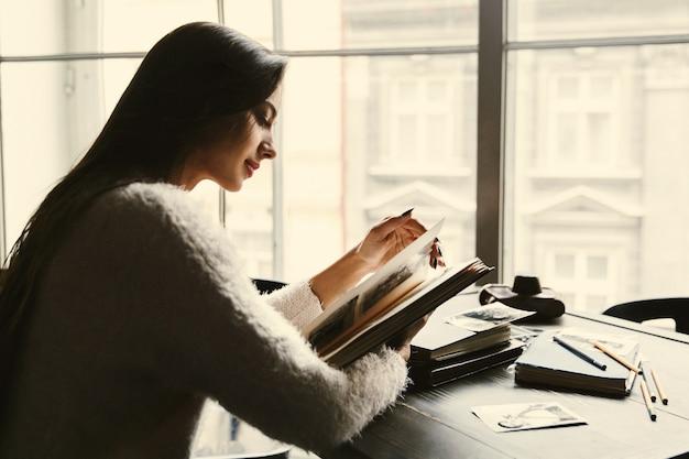 Verträumte dame sitzt mit alten fotoalben im café