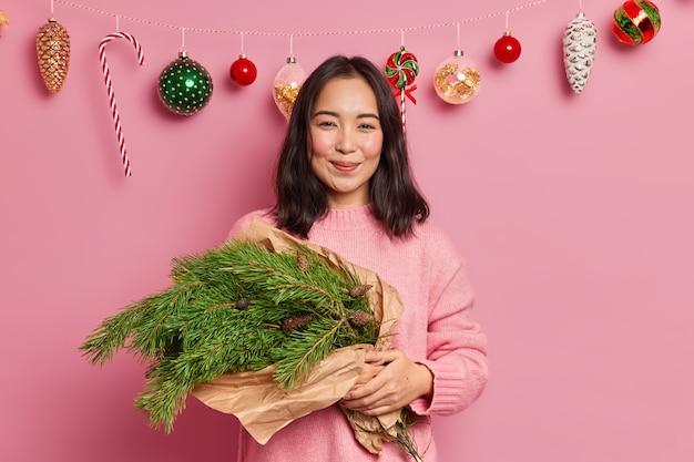 Verträumte erfreute asiatische frau hält handgemachten neujahrsstrauß aus grünen fichtenzweigen gekleidet in lässigem pullover bereitet sich auf winterferien vor