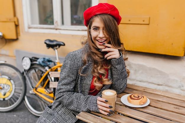 Verträumte frau, die kaffee und kuchen nach dem fahrradfahren genießt