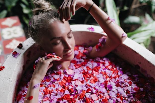 Verträumte frau, die mit geschlossenen augen im bad voller rosa rosen liegt. überkopfaufnahme der romantischen dame mit gebräunter haut, die während des spa am morgen abkühlt.