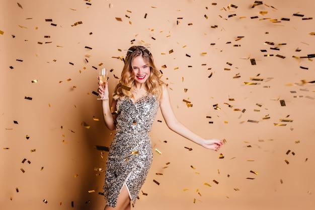 Verträumte frau im eleganten funkelnden kleid, das mit weinglas tanzt und lächelt