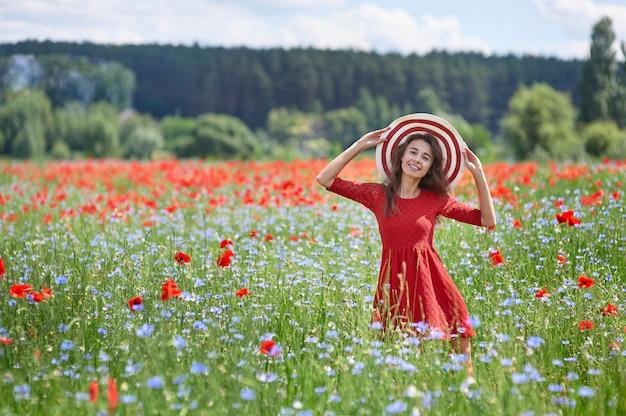 Verträumte frau im roten kleid und im großen roten gestreiften hut im schönen mohnfeld der kräuterblüte