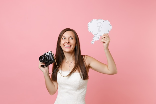 Verträumte frau im weißen kleid hält retro-vintage-fotokamera, sagen sie wolkensprechblase mit glühbirne, die personal wählt, fotograf