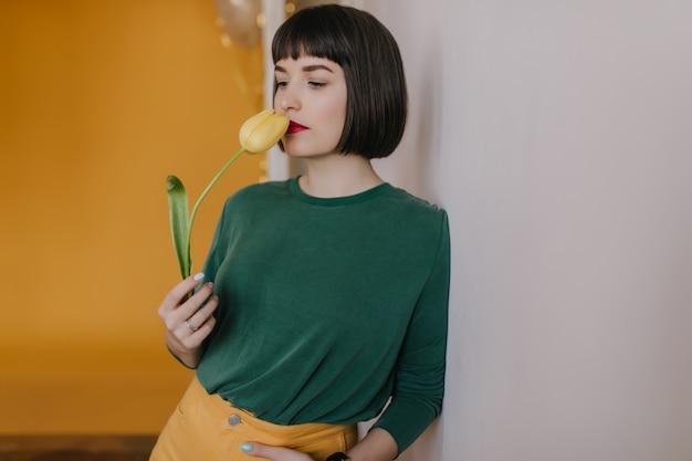 Verträumte frau in freizeitkleidung schnüffelt an gelber tulpe. innenfoto des entzückenden weißen mädchens mit blume, die zu hause aufwirft.