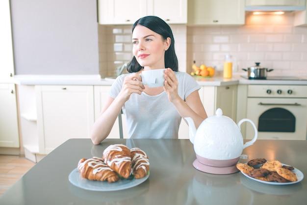 Verträumte frau sitzt am tisch und schaut nach rechts. sie hält weiße tasse in händen. es gibt wasserkocher und teller mit keksen und croissans am tisch.
