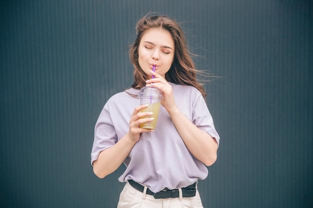 Verträumte frau trinken cocktail oder limonade und genießen es mit geschlossenen augen