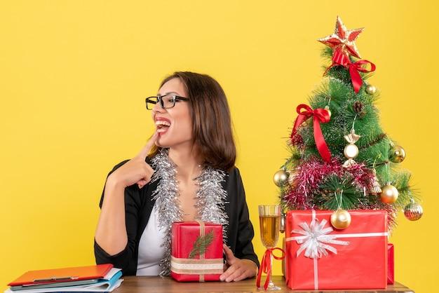 Verträumte geschäftsdame im anzug mit brille, die ihr geschenk hält, etwas betrachtet und an einem tisch mit einem weihnachtsbaum darauf im büro sitzt