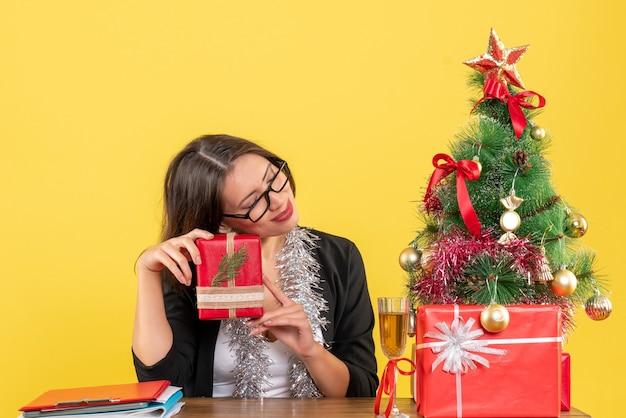Verträumte geschäftsdame im anzug mit brille, die ihr geschenk hält und an einem tisch mit einem weihnachtsbaum darauf im büro sitzt