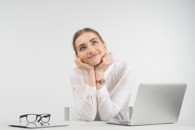Verträumte geschäftsfrau sitzt neben einem laptop und schaut auf und legt ihren kopf auf die arme