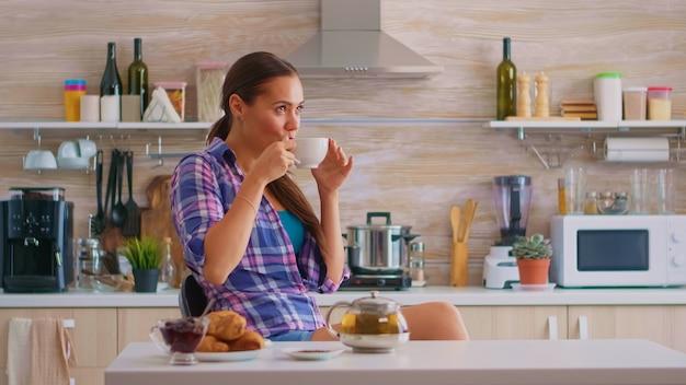 Verträumte glückliche frau, die einen großen morgen hat, der heißen grünen tee trinkt. fröhliche dame, die während des frühstücks in der küche sitzt und sich mit leckerem natürlichen kräutertee aus weißer teetasse entspannt.