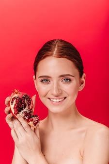 Verträumte ingwerfrau, die granat hält und lacht. glückliches nacktes mädchen, das mit granatapfel auf rotem hintergrund aufwirft.