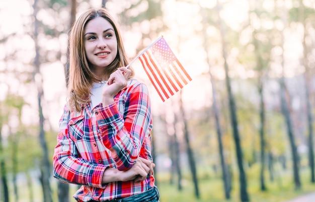 Verträumte junge frau mit kleiner amerikanischer flagge