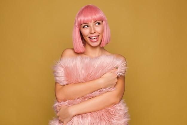 Verträumte junge reizende fröhliche frau mit rosa bob-frisur, die ihre zunge herausstreckt, während sie glücklich beiseite schaut und rosa pelziges kissen umarmt, während sie über senfwand aufwirft