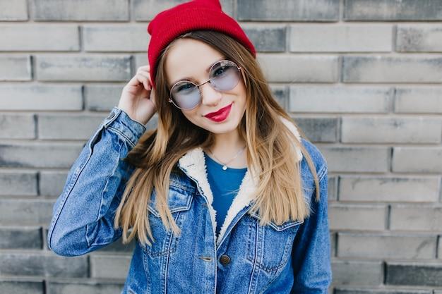 Verträumte kaukasische frau in den trendigen kleidern auf ziegelmauer