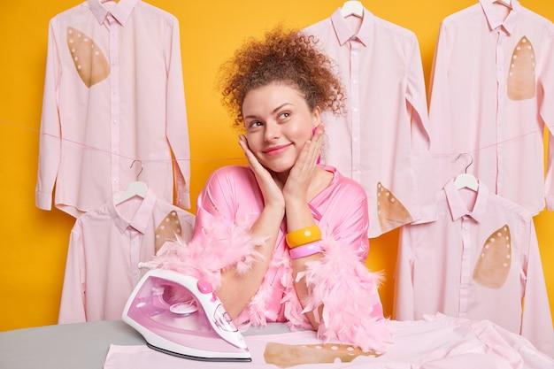 Verträumte, lockige hausfrau posiert in der nähe eines bügelbretts, das tief in gedanken träumt, während sie hausarbeit macht, bügelt frisch gewaschene kleidung einzeln über gelber wand. zimmermädchen räumt wäsche auf