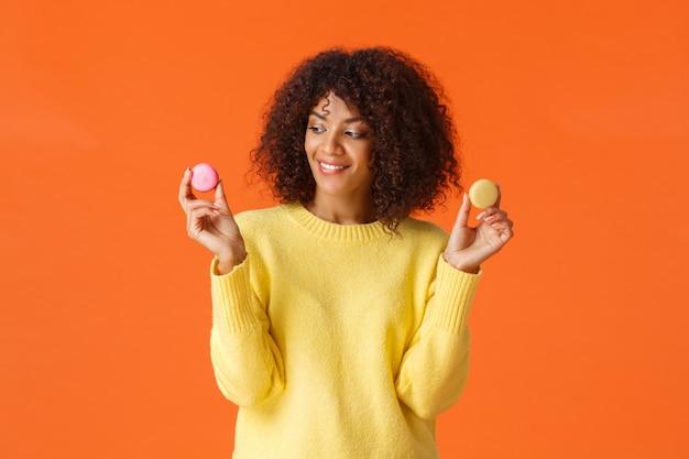 Verträumte nette moderne afroamerikanerfrau des oberkörperporträts behandeln sich und essen nachtische am betrügerischen tag, überspringen die diät, halten zwei geschmackvolle macarons und lächeln, wie die bonbons und stehen orange