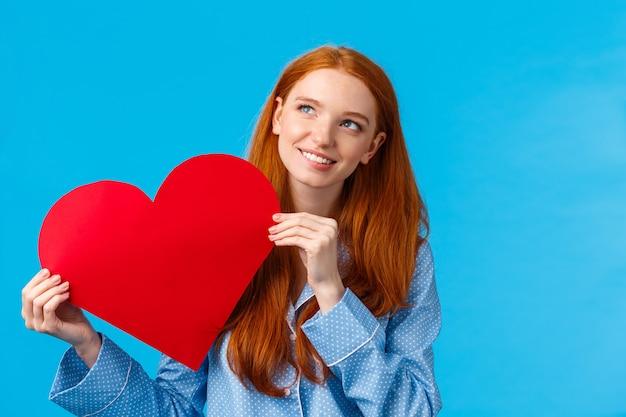 Verträumte romantische teenager-mädchen denken, wie valentinstag karte zum liebhaber geben