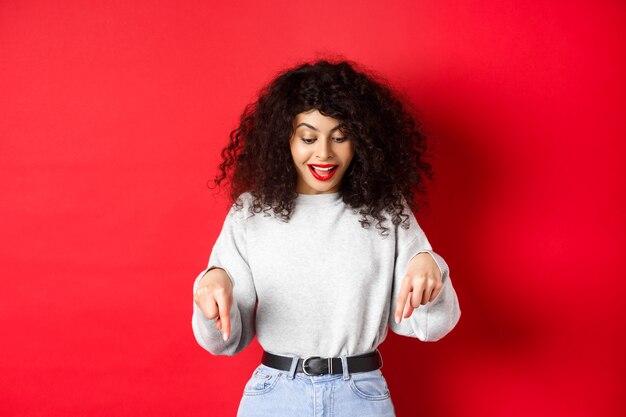 Verträumte schöne frau mit lockigem haar, zeigt und schaut aufgeregt nach unten, prüft promo, steht gegen roten hintergrund.