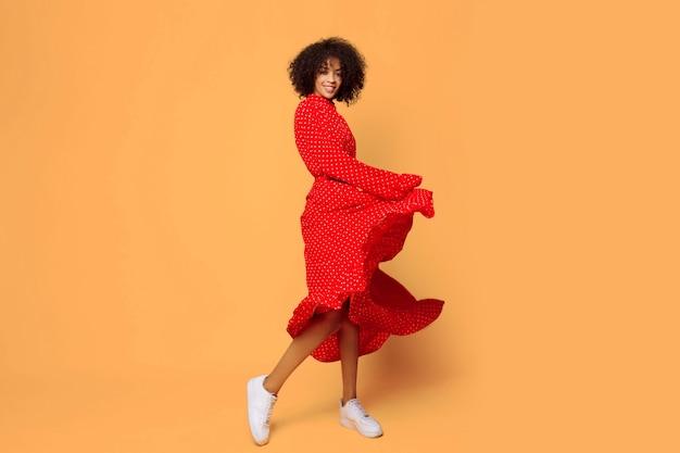 Verträumte stimmung. stilvolles afrikanisches mädchen, das auf orange tanzt und springt