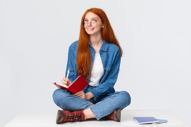 Verträumte und kreative niedliche fleißige studentin mit roten haaren, in gläsern, sitzend auf dem boden mit gekreuzten beinen, umgeben von notizbüchern, die etwas schreiben