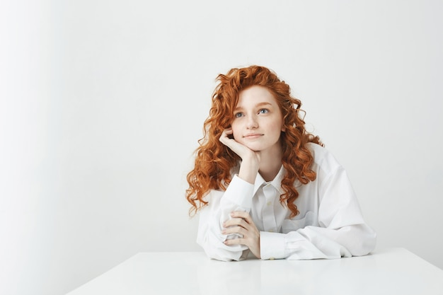 Verträumte zarte junge frau mit dem roten lockigen haar, das das träumen denkt, das auf tisch sitzt.