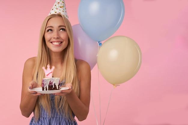 Verträumte ziemlich langhaarige blonde frau, die ein stück kuchen mit kerze hält und glücklich lächelt und über rosa hintergrund mit bündel von mehrfarbigen heliumballons aufwirft