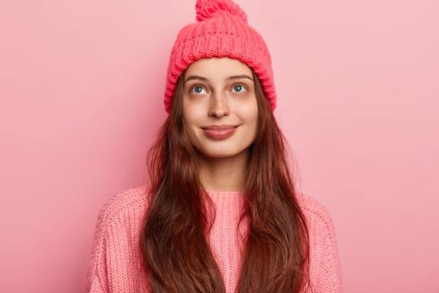 Verträumte zufriedene brünette tausendjährige mädchen schaut oben mit angenehmen gedanken, trägt lebendige strickmütze und pullover, modelle über rosa hintergrund, hat charmantes lächeln und zarten blick