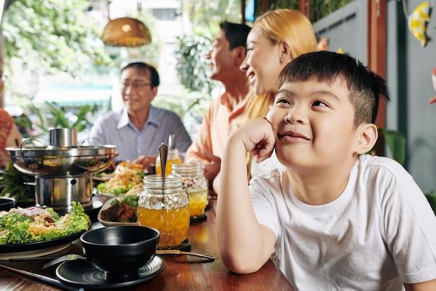 Verträumter junge bei familienfeier