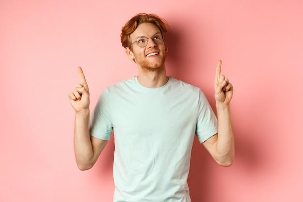 Verträumter junger mann mit roten haaren und bart, der mit den fingern zeigt und fröhlich aufschaut, bewundern etwas ...