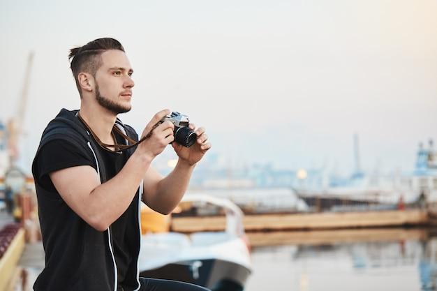 Verträumter talentierter kameramann beeindruckt von der schönheit der natur, während er fotos vor der kamera macht, den blauen himmel betrachtet und im hafen in der nähe des meeres steht. kerl, der schöne aufnahmen von meerblick beim gehen einfängt