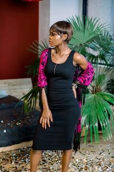 Verträumtes afrikanisches mädchen im schwarzen kleid feiern, wunsch machen. frauentag, happy new year geburtstag mockup urlaub party konzept