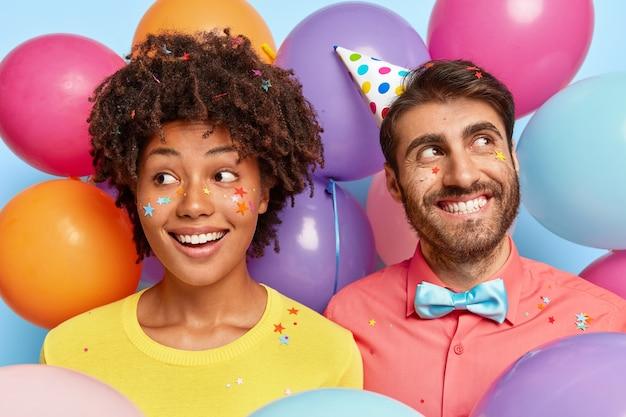 Verträumtes fröhliches junges paar posiert umgeben von bunten luftballons zum geburtstag