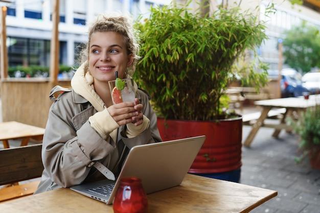 Verträumtes glückliches mädchen, das einen drink in einem café genießt, während pausenarbeit hat.
