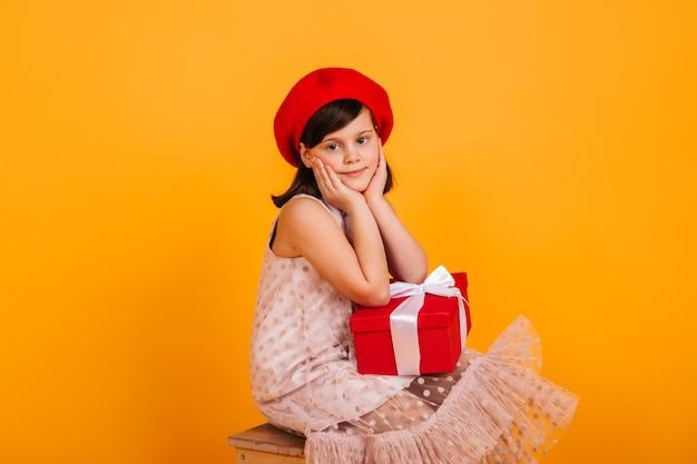 Verträumtes kind, das mit geburtstagsgeschenk aufwirft. preteen mädchen in der roten baskenmütze, die neujahrsgeschenk hält.