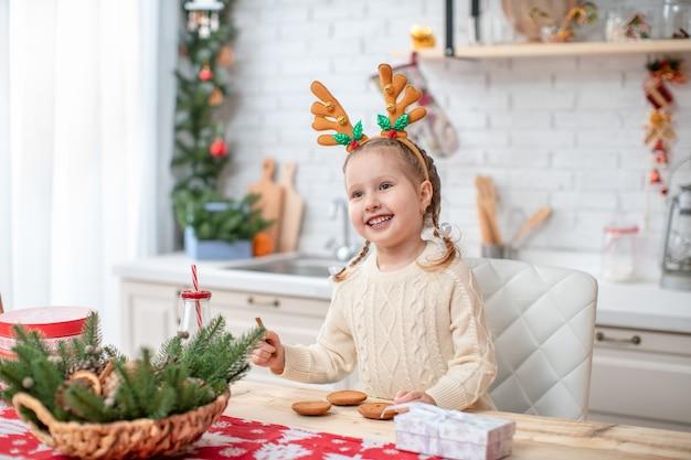 Verträumtes kind in leichtem pullover und stirnband mit rentierhörnern