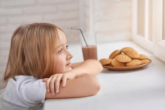 Verträumtes kleines mädchen mit keksen auf fensterbank