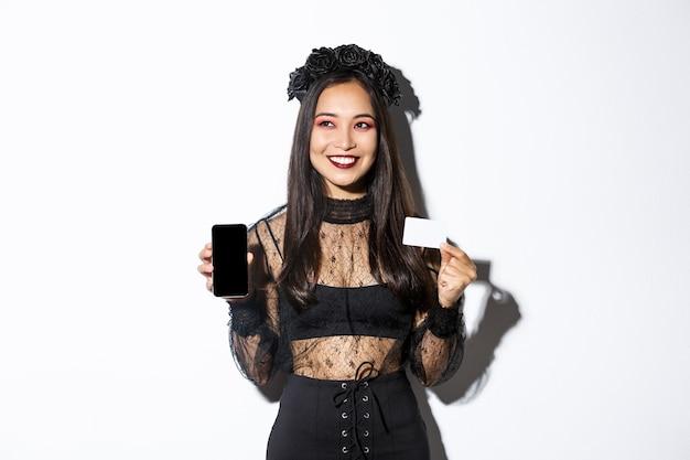 Verträumtes lächelndes mädchen, das weg schaut, während denkend, kreditkarte und handy zeigend, halloween-gothic-kleid tragend.