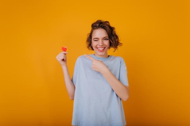 Verträumtes lächelndes mädchen mit herz in der hand, die spaß während des fotoshootings hat. wunderbare lockige frau, die im studio am valentinstag kühlt.