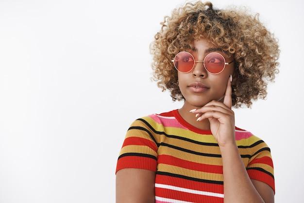 Verträumtes mädchen, das als denken wegschaut. charmante stylische afroamerikanische frau im trendigen 90er-jahre-outfit mit cooler roter sonnenbrille, die nachdenklich und entspannt mit einem leichten lächeln in die obere linke ecke blickt